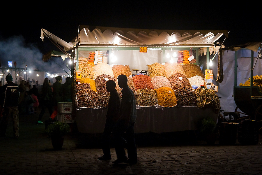 Two men walk past a bright market stall selling nuts and dried fruit on the Djemaa El-Fna square in the heart of the Marrakech medina, Morocco on November 14, 2007. The plaza bustles with food stalls and performers of all sorts till late every night.