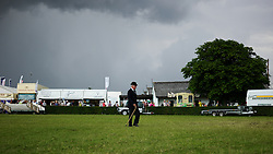 © Licensed to London News Pictures. <br /> 08/07/2014. <br /> <br /> Harrogate, United Kingdom<br /> <br /> A man walks across the green during the first day of the Great Yorkshire Show. The show is England's Premier Agricultural Event and is based on the 250-acre Great Yorkshire Showground near Harrogate. The Main Ring is the hub of the Show providing a setting for international show jumping and world class cattle parade. The showground is filled with animals, country demonstrations, have-a-go activities and rural crafts.<br /> <br /> Photo credit : Ian Forsyth/LNP