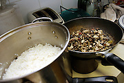 Mushrooms and rice recovered from dumping sites around the island of Manhattan, New York, NY., being cooked during a Freegan dinner, on Friday, June 23, 2006. Freegans are a community of people who aims at recovering wasted food, books, clothing, office supplies and other items from the refuse of retail stores, frequently discarded in brand new condition. They recover goods not for profit, but to serve their own immediate needs and to share freely with others. According to a study by a USDA-commissioned study by Dr. Timothy Jones at the University of Arizona, half of all food in the United States is wasted at a cost of $100 billion dollars every year. Yet 4.4 million people in the United States alone are classified by the USDA as hungry. Global estimates place the annual rate of starvation deaths at well over 8 million. The massive waste generated in the process fills landfills and consumes land as new landfills are built. This waste stream also pollutes the environment, damages public health as landfills chemicals leak into the ground, and incinerators spew heavy metals back into the atmosphere. Freegans practice strategies for everyday living based on sharing resources, minimizing the detrimental impact of our consumption, and reducing and recovering waste and independence from the profit-driven economy. They are dismayed by the social and ecological costs of an economic model where only profit is valued, at the expense of the environment. In a society that worships competition and self-interest, Freegans advocate living ethical, free, and happy lives centred around community and the notion that a healthy society must function on interdependence. Freegans also believe that people have a right and responsibility to take back control of their time.