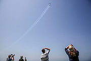 """People watch from a rooftop as an Israeli Air Force (IAf) """"Efroni"""" (T-6 Texan II) plane performs an aerobatic maneuver during Independence Day celebrations in Tel-Aviv, Israel April 15, 2021. People gathered in their masses at Tel-Aviv's shore line as the Jewish state celebrates 73 years to it's establishment. As vast percentage of the population are vaccinated, celebrations were able to take place in a some what ordinary manner.Starting Sunday April 18, 2021, it will no longer be mandatory to wear a protective mask in open spaces throughout the country."""
