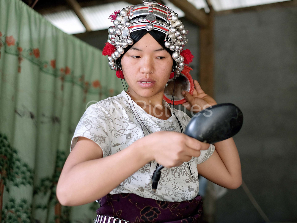 An Akha woman putting on her traditional headdress before a village wedding, Ban Lang Pa, Luang Namtha province, Lao PDR. Made from hand forged silver, coins, handwoven cotton, market bought cotton, plastic beads, bamboo, cowrie shells and woollen tassels women would traditionally wear their headdress even while bathing, sleeping and working in the fields.
