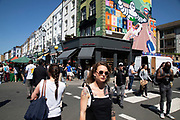 Michellin Man street art on the side of a building on Portobello Road in Notting Hill, West London, England, United Kingdom. People enjoying a sunny day out hanging out at the famous Sunday market, when the antique stalls line the street.  Portobello Market is the worlds largest antiques market with over 1,000 dealers selling every kind of antique and collectible. Visitors flock from all over the world to walk along one of Londons best loved streets.