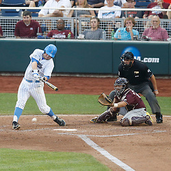 Jun 25, 2013; Omaha, NE, USA; UCLA Bruins second baseman Cody Regis (left) hits a RBI-single in front of Mississippi State Bulldogs catcher Nick Ammirati (right) during the fourth inning in game 2 of the College World Series finals at TD Ameritrade Park. Mandatory Credit: Derick E. Hingle-USA TODAY Sports