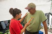 Farmer and owner of Gathering Together Farm John Eveland and Lane Selman talk vegetables.