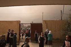 Licensed to London News Pictures. 08/11/2016. Qayyarah, Iraq. Smoke from burning oil facilities fills the air as children at the Al Rumana School assemble for lessons in Qayyarah, Iraq. Oil wells in and around the town of Qayyarah, Iraq, we set alight in July 2016 by Islamic State extremists as the Iraqi military began an offensive to liberated the town.<br /> <br /> For two months the residents of the town have lived under an almost constant smoke cloud, the only respite coming when the wind changes. Those in the town, despite having been freed from ISIS occupation, now live with little power, a water supply tainted with oil that only comes on periodically and an oppressive cloud of smoke that coats everything with thick soot. Many complain of respiratory problems, but the long term health implications for the men, women and children living in the town have yet to be seen. Photo credit: Matt Cetti-Roberts/LNP