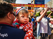 "08 FEBRUARY 2016 - BANGKOK, THAILAND:  A man carries his child through the New Year's parades in Bangkok's Chinatown district during the celebration of the Lunar New Year. Chinese New Year is also called Lunar New Year or Tet (in Vietnamese communities). This year is the ""Year of the Monkey."" Thailand has the largest overseas Chinese population in the world; about 14 percent of Thais are of Chinese ancestry and some Chinese holidays, especially Chinese New Year, are widely celebrated in Thailand.      PHOTO BY JACK KURTZ"