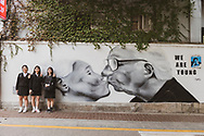 """Three high school seniors stand next to a mural of a kissing older couple that reads """"we are young"""" in Seoul, South Korea. (September 27, 2019)"""