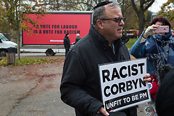London, UK. 26 November, 2019. A man holding a sign reading 'Racist Corbyn Unfit To Be PM' is interviewed outside the Bernie Grant Arts Centre in Tottenham before the arrival of Labour Party leader Jeremy Corbyn to launch Labour's new Race and Faith Manifesto.