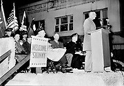 """9305-A4609-2. General Wainwright speaks into a KODL microphone at a war bond drive in The Dalles, Oregon, on East Second Street in front of the Granada theatre, November 15, 1945. A sign says """"Welcome Skinny"""". Wainwright was a four star general who had recently been liberated from thirty nine months of captivity as a Japanese prisoner of war.  At the time, he was America's most famous hero of the war, having endured the Battan Death March and torture in captivity.  He was making a national tour of appearances to promote the war bond drive."""