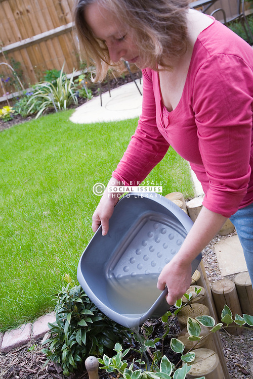 Woman watering the garden with washing up water,