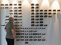 "SOLMS, GERMANY - MAY-18-2009 - Ralph Hagenauer, Leica's head of Product Communications, looks at the ""Leica Family Tree"" display, in the lobby of Leica's HQ in Solms, Germany. (Photo © Jock Fistick)"