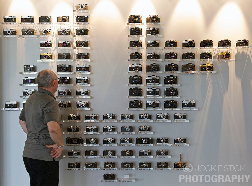 """SOLMS, GERMANY - MAY-18-2009 - Ralph Hagenauer, Leica's head of Product Communications, looks at the """"Leica Family Tree"""" display, in the lobby of Leica's HQ in Solms, Germany. (Photo © Jock Fistick)"""