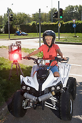 Boy with quadbike on driver training area with speed trap