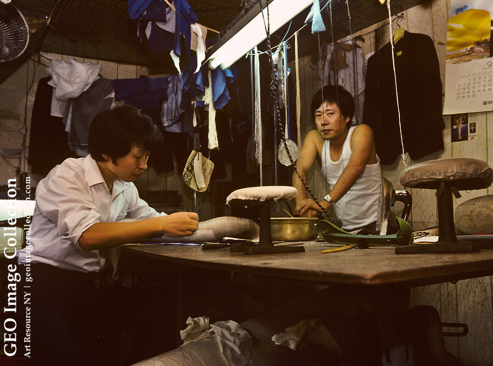 Garment workers laboring in a small clothing tailor shop in Seoul, South Korea. The shop has eight workers and typical of small garment sweatshop workrooms. The men are making men's suits. Laborers in the garment industry may work 16-hour days.