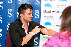 "Peter Andre shows a tatoo to one of his fans during a  book signing event for  his new childrens books ""The Happy Birthday Party"" and ""A New Day at School"" in WH Smiths Sheffield on 6th September 2011 .Image © Paul David Drabble"