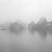 A tranquil scene as early morning mist surrounds Ha Long Bay, Vietnam. The bay consists of a dense cluster of 1,969 limestone monolithic islands. Ha Long Bay, is a UNESCO World Heritage Site, and a popular tourist destination. Ha Long, Bay, Vietnam.  Photo Tim Clayton