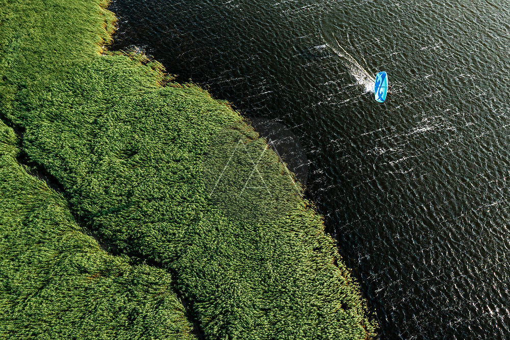 Aerial view of kiteboarder surfing in wild nature landscape in Klaipėda, Svencele, Lithuania.