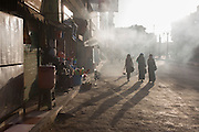 Three Egytptian women walk through smoky air, emitted from a kebab business on a street in Luxor, Nile Valley, Egypt.