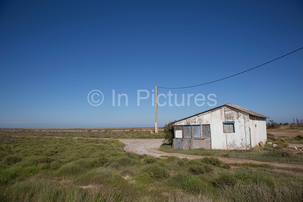 Small boarded up house under a telephone wire under a blue sky at Gruissan, Languedoc-Roussillon, France.