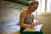 A young female prisoner writing a letter in her cell. HM Prison Styal is a Closed Category prison for female adults and young offenders, located in the village of Styal (near Wilmslow) in Cheshire, England. The prison is operated by Her Majesty's Prison Service. Styal is a Closed Category prison for sentenced and remanded female adults and young offenders. There are also facilities for mothers with babies up to age 18 months. The education provision at Styal is contracted out to The Manchester College. Courses offered include hairdressing, information technology, art and design, ESOL, catering, industrial cleaning, painting & decorating, and Open University support.