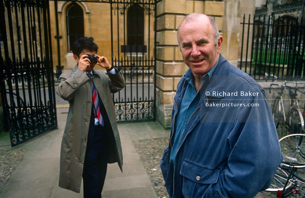 A portrait of Australian-born, Clive James as he is recognised and photographed by a Japanese tourist, on 20th January 1990 in Cambridge UK. Clive James AO CBE FRSL (1939-2019) was an Australian author, critic, broadcaster, poet, translator and memoirist, best known for his autobiographical series Unreliable Memoirs, for his chat shows and documentaries on British television and for his prolific journalism. He has lived and worked in the United Kingdom since 1962.