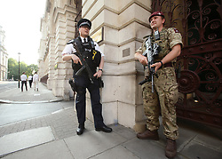 "A police officer and a soldier on duty outside the Foreign and Commonwealth Office, London, as armed troops have been deployed to guard ""key locations"" under Operation Temperer, which is being enacted after security experts warned the Government that another terrorist attack could be imminent."