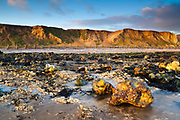 Low tide at West Runton reveals a beach scattered with flints, chalk and other glacial deposits. Overlooked by crumbling cliffs. North Norfolk, East Anglia.