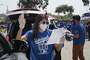 Volunteers direct motorists at the Dodger Day Drive-Thru at Belvedere Park, Tuesday, June 30, 2020, in Los Angeles. The event was hosted by The Los Angeles Dodgers Foundation, which distributed food boxes, books, sports equipment, clothing, toys and hygiene supplies to more than 1,000 registered youth from the Boyle Heights, East Los Angeles, La Puente and Monterey Park communities.