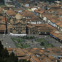 Churches, cathedral, businesses and tile-roofed houses surround a central square of Cuzco, Peru.