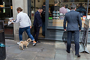 Passers-by step over a pet dog, tied-up and waiting for its owner who is inside a sandwich business during the lunchtime rush on Watling Street, the former Roman thoroughfare, in the City of London, (aka The Square Mile) the capital's financial district, on 3rd September 2019, in London, England.