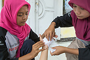 Members of Belanting's emergency preparedness team Zilpi Hilwani, 22 (left), and Hairia, 19 (right), practice their first aid skills during a drill, applying a bandage on the hand of fellow team member Herlinawati, 18. Belanting is located in Sambelia district, East Lombok, West Nusa Tenggara province, Indonesia.