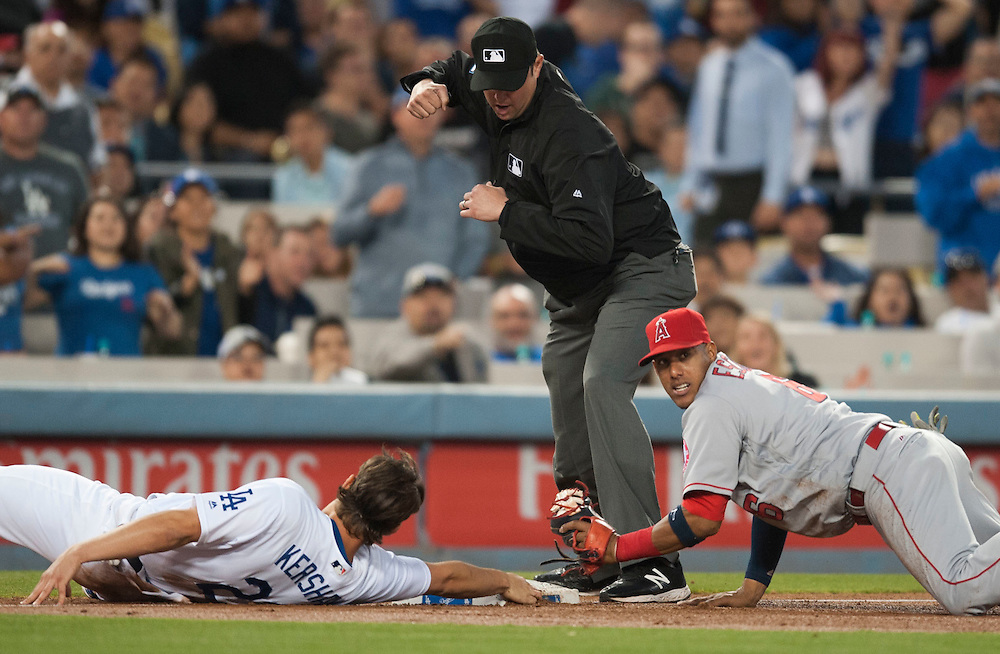 The Dodgers' Clayton Kershaw is called out by third base umpire Jordan Baker as the Angels' Yunel Escobar looks to the bench in the third inning after being thrown out by Mike Trout trying to stretch Tuesday night at Dodger Stadium.<br /> <br /> / //ADDITIONAL INFO:   <br /> <br /> angels.0518.kjs  ---  Photo by KEVIN SULLIVAN / Orange County Register  -- 5/17/16<br /> <br /> The Los Angeles Angels take on the Los Angeles Dodgers in inter-league play at Dodger Stadium Tuesday night.