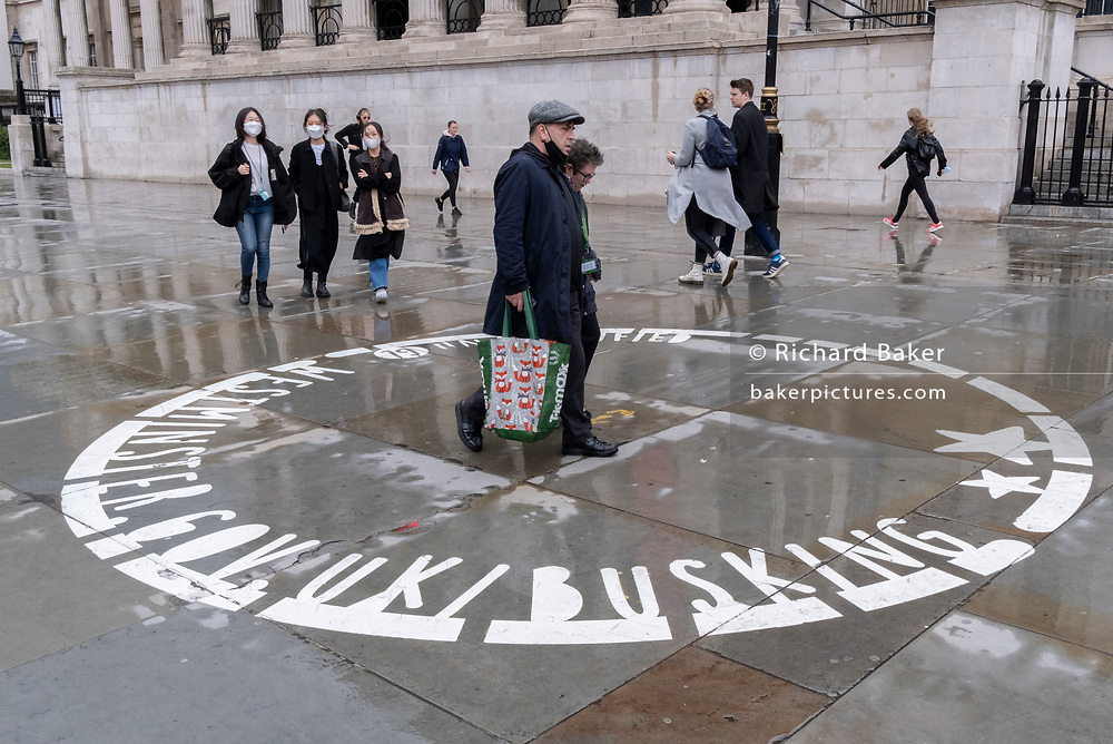 After seasonal Spring rainfall, Londoners walk past an empty busker's circle, on the paved area in front of the National Gallery in Trafalgar Square on 24th May 2021, in London, England.
