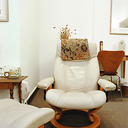 """A white leather Stressless chair and footrest on a greyish brown office carpet in a white room. There is a small wooden antique table to the left, at a corner in the room, with a clock, floral tissue box, and ceramic cosater on it. a white phone hanging low on the wall behind the table and by the chair. There is a wooden Scandanavian desk chair and table behind the chair, with two small sculptures and a """"Monet's Years"""" poster above, a small woven trash can and clear plastic bag in the right corner."""