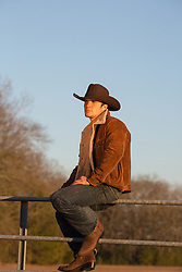 All American Cowboy on a ranch gate at sunset