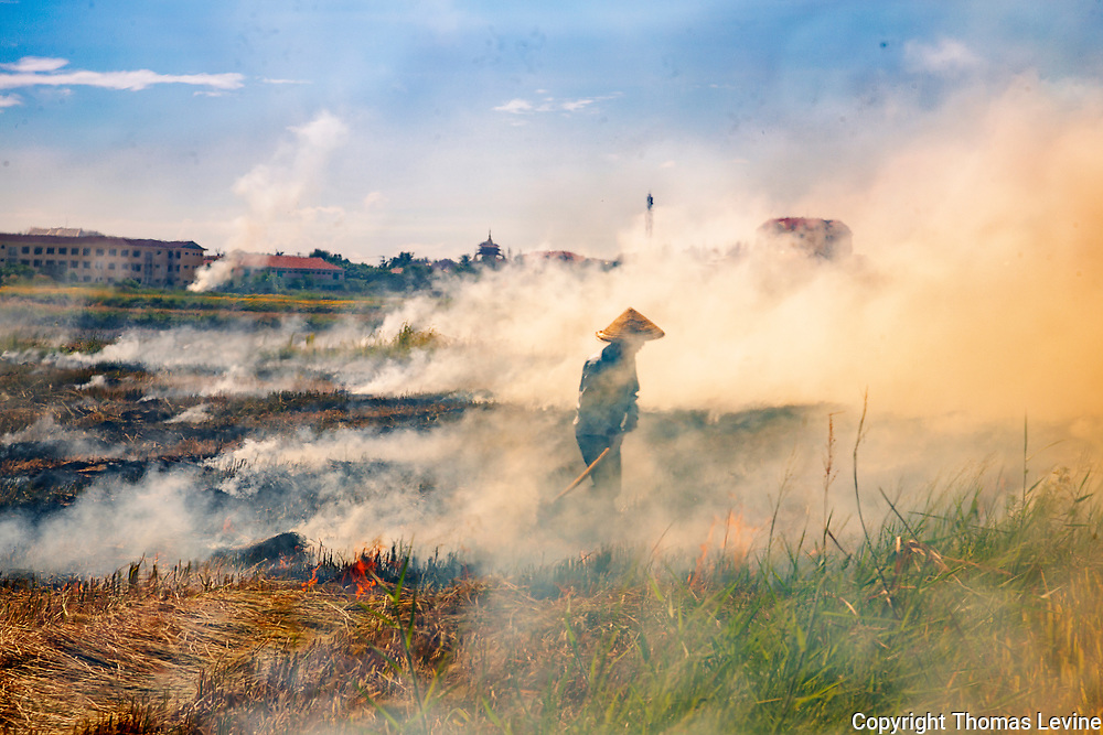 Rice Farmer stands in the thick of smoke after harvest in Hoi An, Vietnam