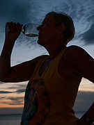 """Redington Beach. Florida, USA,  """"cheers"""" Silhouette of women finishing a glass of wine.<br /> <br /> <br /> Monday 03/10/2016<br /> <br /> © Peter SPURRIER,<br /> <br /> LEICA DIGILUX 2. ISO 100  f2.4  Lens 22.5mm   3.6MB"""