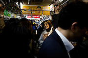 TOKYO, JAPAN - 30 MARCH - A woman smile in a crowded train. March 2012