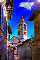 """""""The bell tower of Santa Chiara in Assisi rises high in the sky""""…<br /> <br /> After a progressive but slow assent up to the mountaintop of Assisi, I took time to pause, look over my shoulder, and truly appreciate all I had seen.  God always seemed to illuminate my forward path; however, He also left a glow of remembrance from where the journey began. This evening view is of the campanile from the Basilica di Santa Chiara. This 13th-century church houses the relics of St. Clare, friend and protégé of St. Francis of Assisi, and the 12th-century crucifix that spoke to St. Francis at San Damiano. The churches, Basilicas, Duomos, and all the spiritual history of this tiny hilltop village, force one to realize the blessings of the Saints who traversed the same footsteps as we walk today.  It is remarkable to imagine that seven Saints originated from Assisi over a 15 century period.  What a great percentage of the blessed from such a small town!  Assisi is perhaps one of the most visited pilgrimage areas in the world, and people from all races and religions come here to experience and find the peace which has blessed so many.  They say that one can almost hear all the prayers lifted up from the walls of this most spiritual of places."""