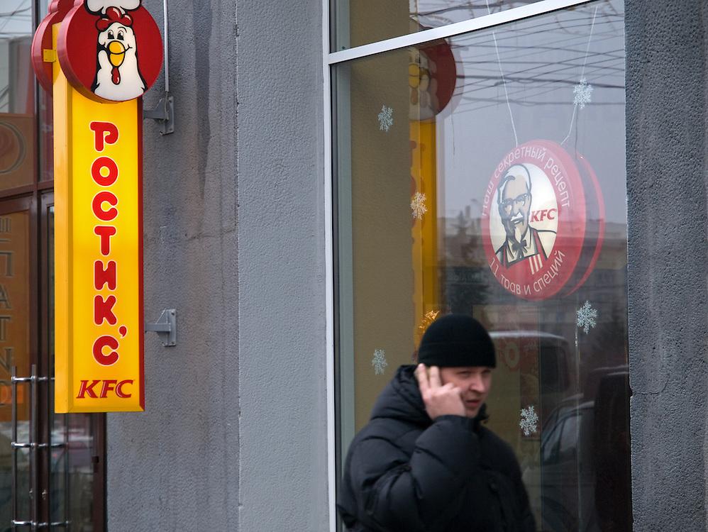 Nowosibirsk/Russische Foederation, RUS, 19.11.07: Passant vor der Kentucky Fried Chicken (KFC) Filiale im Zentrum der sibirischen Hauptstadt Nowosibirsk.<br /> <br /> Novosibirsk/Russian Federation, RUS, 19.11.07: Passerby in front of the Kentucky Fried Chicken (KFC) chain store in the Sibirian capitol Novosibirsk.