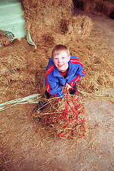 Young boy with Downs syndrome holding hay bale smiling,