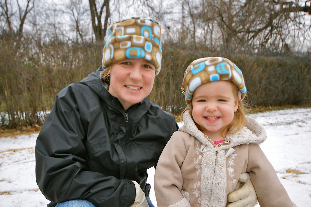 Happy mother and daughter with similar hats pose in snow