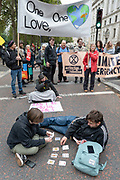Extinction Rebellion protesters playing cards at a roadblock at St Jamess Park on the 7th October 2019 in Central London in the United Kingdom. Extinction Rebellion protesters occupy locations across central London including Westminster Bridge, Whitehall and Trafalgar Square in a wave of protests planned to continue for 2 weeks.