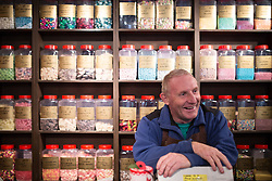 """© Licensed to London News Pictures . 17/11/2014 . Kent , UK . Shop owner , JOHN BALDOCK , of """" Sweet Expectation """" who is displaying coloured sweets on illustrating the voting intentions of its customers in the window of his shop , on High Street Rochester , ahead of the Rochester and Strood by-election . Photo credit : Joel Goodman/LNP"""