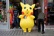 Promotional Pokemon Pikatchu stands outside a dressing up shop as people go about their daily business on Berwick Street in Soho, London, United Kingdom. Pikachu are a species of Pokemon, fictional creatures that appear in an assortment of video games, animated television shows and movies, trading card games, and comic books licensed by The Pokémon Company, a Japanese corporation.
