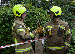 © Licensed to London News Pictures. 23/08/2019. London, UK. Fire fighters pass a pick at the scene where a fire has started at a flat in a tower block at Darfield Way in west London, just yards from Grenfell Tower. Photo credit: Ben Cawthra/LNP
