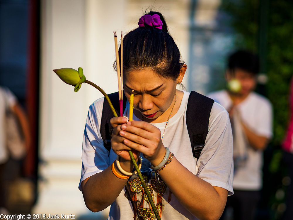 """01 MARCH 2018 - BANGKOK, THAILAND: A woman prays at Wat Pathum Wanaram in central Bangkok. Many people go to temples to perform merit-making activities on Makha Bucha Day, which marks four important events in Buddhism: 1,250 disciples came to see the Buddha without being summoned, all of them were Arhantas, or Enlightened Ones, and all were ordained by the Buddha himself. The Buddha gave those Arhantas the principles of Buddhism. In Thailand, this teaching has been dubbed the """"Heart of Buddhism.""""    PHOTO BY JACK KURTZ"""