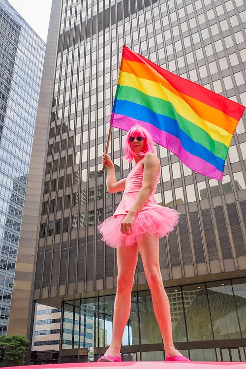 United States, Washington, Seattle Gay Pride Parade, June 28th, 2015. Cross-dressing dancer on top of pink van.