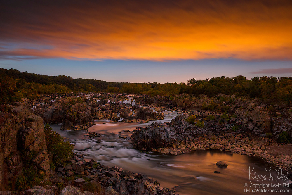 A fiery sunset colors the sky over the Great Falls of the Potomac River, located in Great Falls Park, Virginia. In the park, administered by the National Park Service, the river drops 76 feet (23 meters) in a series of rapids. Great Falls and the Potomac River are located within the state of Maryland, but the main section of the park and the viewing decks are in Virginia.