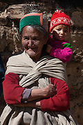 An elderley lady in traditional Kinnauri clothing with a baby on her shoulders, 20th October 2009, Himachal Pradesh, India. The region of Spiti and Kinnaur is a remote and tribal area of the Indian Himalayas near the Tibetan border.